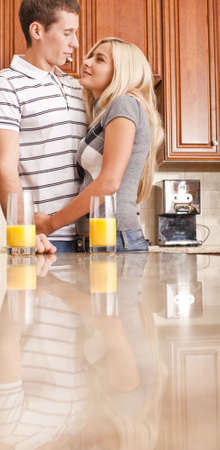 Young couple smiling at each other with glasses of orange juice on counter. Vertical shot. Stock Photo - 6248723