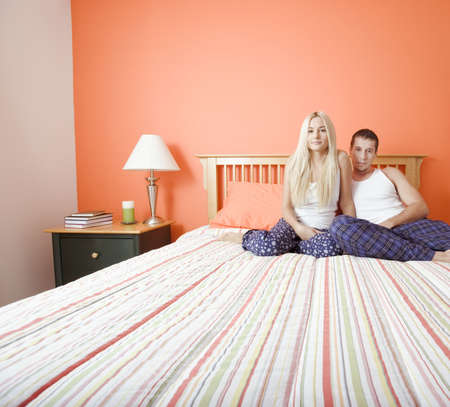 bedspread: Young couple sitting on bed with stripped bedspread. Horizontal shot.