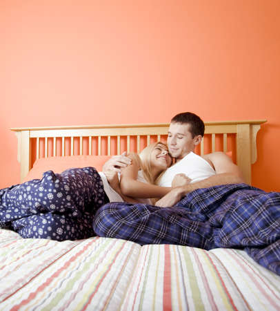 bedspread: Young couple sitting on bed with stripped bedspread facing each other and embracing. Vertical shot. Stock Photo