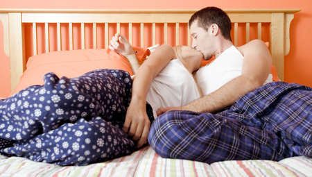 Young couple sitting on bed with stripped bedspread kissing. Horizontal shot.