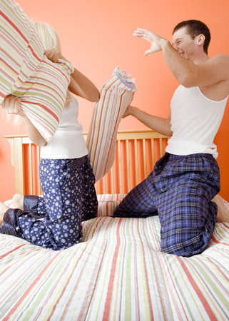 Young couple facing each other, kneeling on bed having a pillow fight. Vertical shot. photo