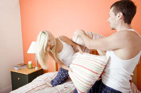 Young couple facing each other, kneeling on bed having a pillow fight. Horizontal shot. photo