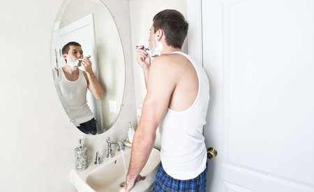 Young man in bathroom looking in the mirror and shaving. Horizontal shot.