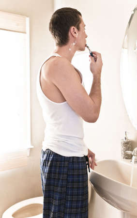 Young man in bathroom looking in the mirror and shaving. Vertical shot. photo
