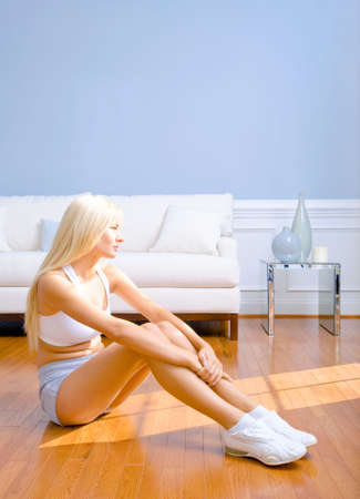 Young woman sitting on floor with arms around drawn up knees. Vertical shot. photo