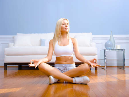 Young woman sitting cross legged on floor with hands on knees meditating. Horizontal shot.
