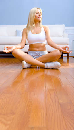 Young woman sitting cross legged on floor with hands on knees meditating. Vertical shot. photo