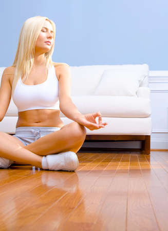 Young woman sitting cross legged on floor with hands on knees meditating. Vertical shot. Stock Photo - 6248867