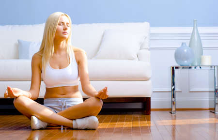 Young woman sitting cross legged on floor with hands on knees meditating. Horizontal shot. Stock Photo - 6248872