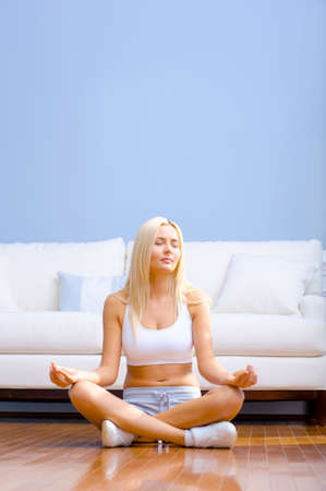 Young woman sitting cross legged on floor with hands on knees meditating. Vertical shot. Stock Photo - 6249111