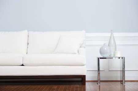 White Sofa und Glas Ende-Tabelle mit Vasen gegen blass blaue Wand festgelegt. Horizontale erschossen.