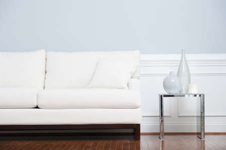 White sofa and glass end table with vases set against pale blue wall. Horizontal shot.