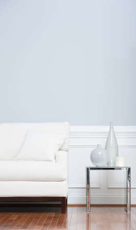 White sofa and glass end table with vases set against pale blue wall. Vertical shot.