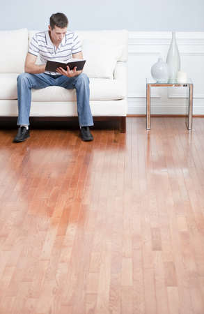 wood flooring: Young man in striped shirt and blue jeans sitting on white sofa reading a book. Vertical shot.