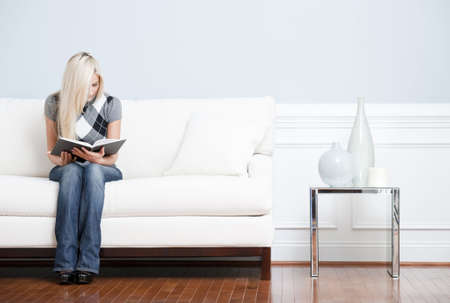 Young woman in checkered shirt and blue jeans sitting on white sofa reading a book. Horizontal shot.