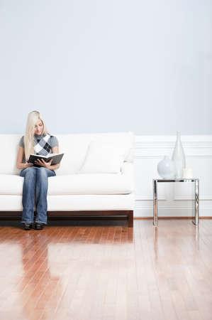 Joven viste un top a cuadros y pantalones vaqueros azul mientras estaba sentado en el sofá blanco.  Ella está leyendo un libro. Un disparo vertical.