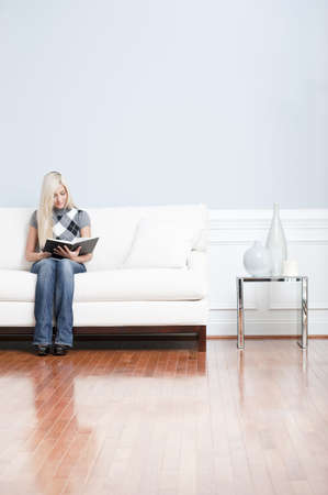 Young woman wears a checkered top and blue jeans while sitting on white sofa.  She is reading a book. Vertical shot.
