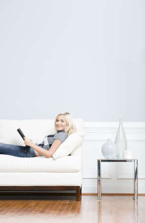 Young woman wears a checkered top and blue jeans lies on a white sofa while reading a book. Vertical shot.