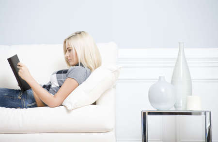 Young woman wears a checkered top and blue jeans, lying on white sofa and reading book. Hoizontal shot. Stock fotó
