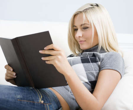 blue  jeans: Young woman wears a checkered top and blue jeans.  She is lying on white sofa and reading a book. Horizontal shot.