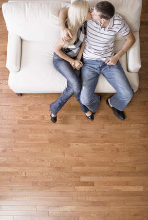 Young couple sitting on a cream colored love seat and kissing. Vertical shot Stock Photo