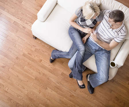wood flooring: Young couple sit on a cream colored love seat and gaze into one anothers eyes. Horizontal shot