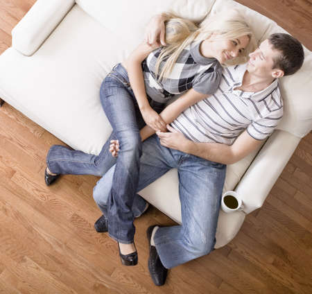 Young couple affectionately sit back on a cream colored love seat. Horizontal shot Stock Photo