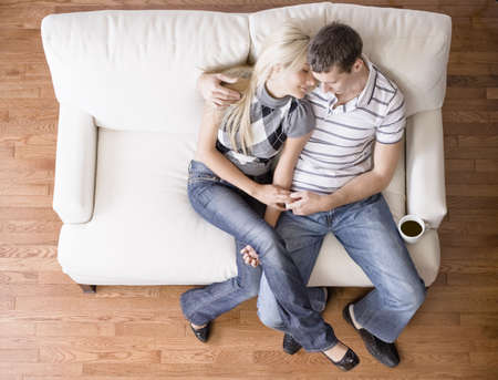 Young couple sit on a cream colored love seat. The man has his arm around the woman. Horizontal shot.