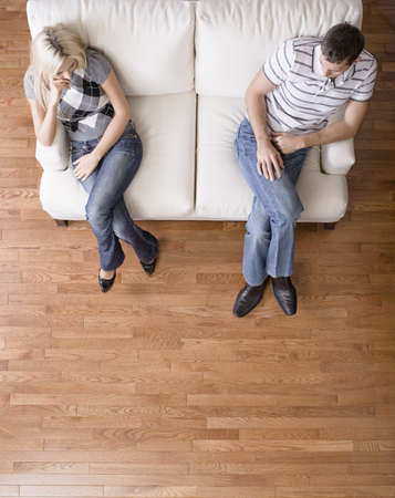 distantly: Man and a woman sit distantly on the ends of a cream colored love seat. Vertical shot.