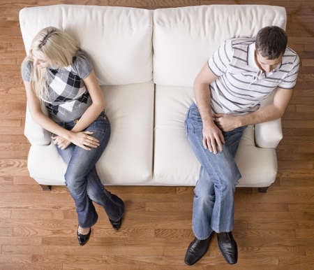 distantly: Man and a woman sit distantly on the ends of a cream colored love seat. Horizontal shot.