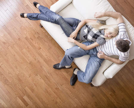 lays: Young woman affectionately lays against a young man on a cream colored love seat. Horizontal shot.