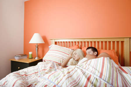couple cuddling: Young couple sleep closely together under a striped bedspread. Horizontal shot.