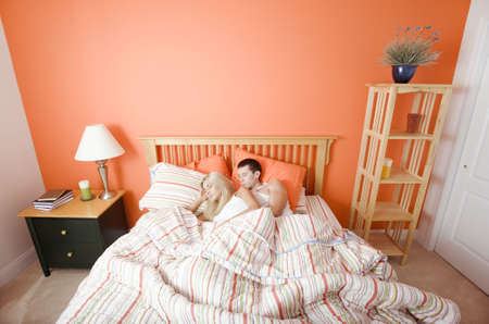 bedspread: High angle view of young couple sleeping closely together under a striped bedspread. Horizontal shot. Stock Photo