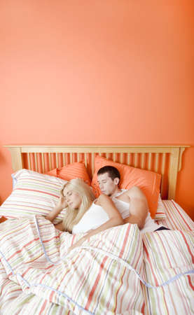 High angle view of young couple sleeping closely together under a striped bedspread. Vertical shot. photo