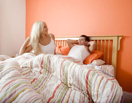 Young couple wake up in bed under a striped bedspread. Horizontal shot. photo