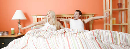 Young couple stretch their arms as they wake up from a striped bed. Horizontal shot. photo