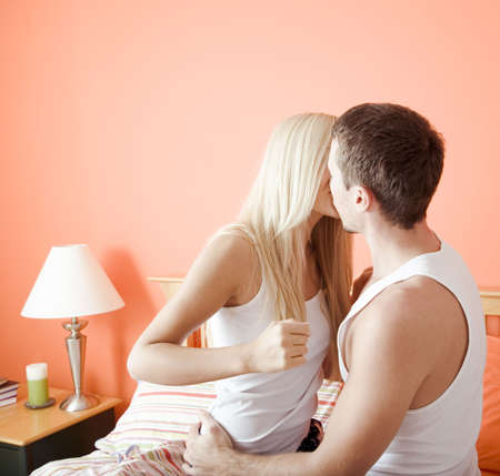 bedroom wall: Young couple wearing white tank tops kiss passionately on the bed. Horizontal shot.