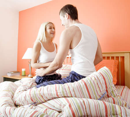 Young couple wearing white tank tops kneel on their bed and smile at each other. Horizontal shot. photo
