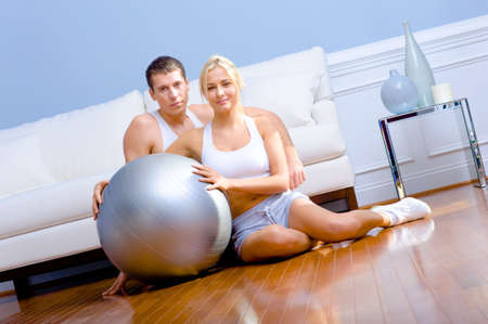 Young couple sit on the wood floor, smiling and holding a silver exercise ball. Horizontal shot. photo