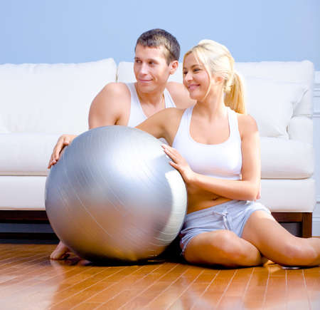 Young couple sit on the wood floor, smiling off to the side while holding a silver exercise ball. Horizontal shot. photo