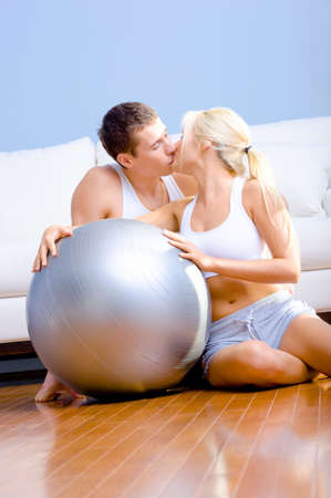 Young couple in sportswear kiss while sitting next to an exercise ball. Vertical shot. photo