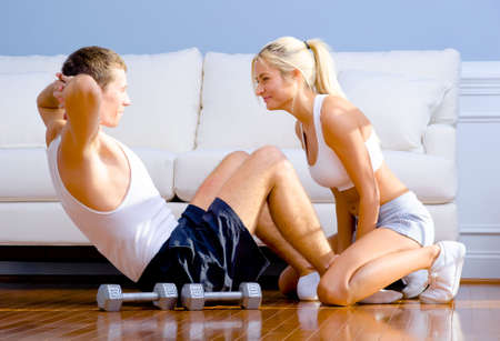 Young man performs sit ups on the floor as a young woman holds his feet. Horizontal shot.