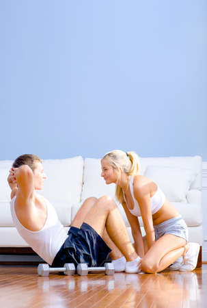 Young man performs sit ups on the floor as a young woman holds his feet. Vertical shot. Stock Photo - 6249184