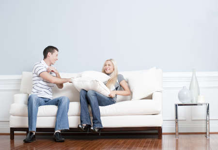 Young man playfully hits a young woman with a pillow on the sofa. Horizontal shot. photo