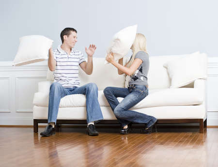 Young couple laugh while having a pillow fight on the sofa. Horizontal shot. photo