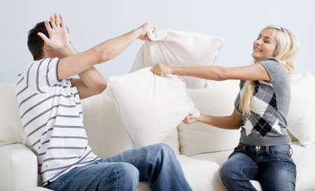 Young man holds his arm up in defense as a young woman playful hits him with a pillow. Horizontal shot.