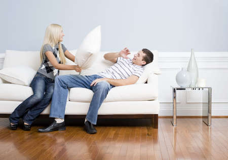 pillow fight: Young couple playfully have a pillow fight on a sofa.  The young man tries to avoid getting hit. Horizontal shot. Stock Photo