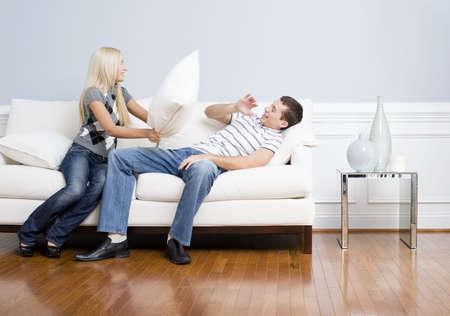 적층: Young couple playfully have a pillow fight on a sofa.  The young man tries to avoid getting hit. Horizontal shot. 스톡 사진