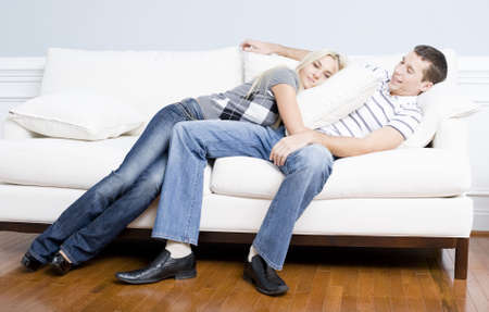 Young couple recline on a white sofa with the young woman lying on the man with a pillow. Horizontal shot. photo