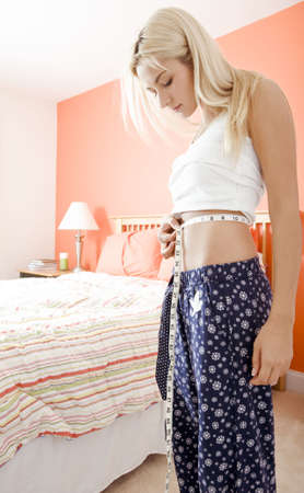 Woman standing in her bedroom and measuring her waist. Vertical format. photo